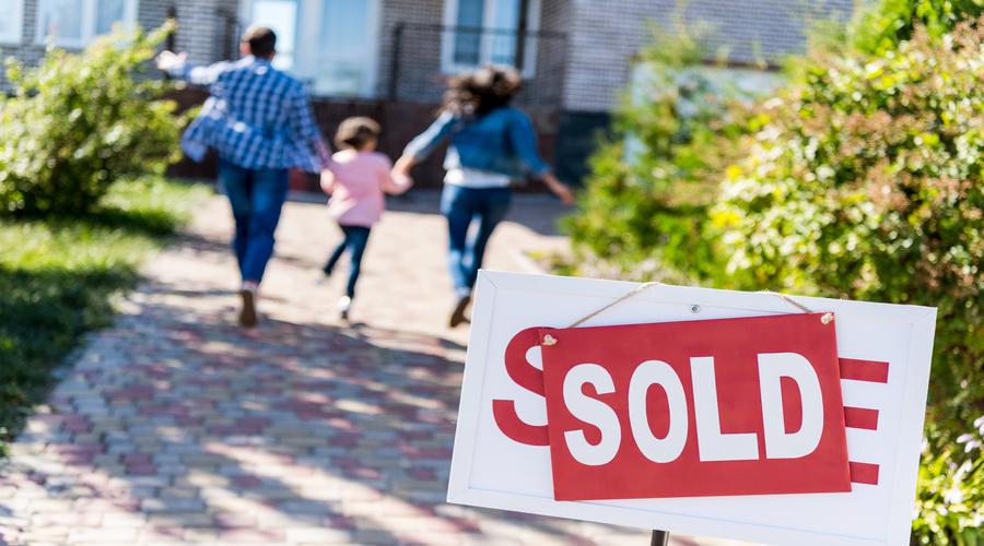 Una familia corre hacia su casa comprada.
